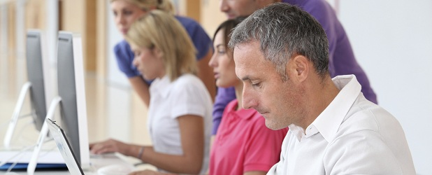 Man sitting at computer watching training video